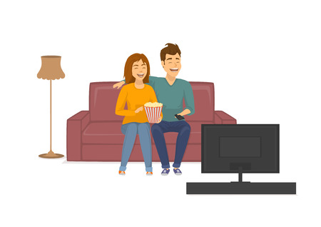 Cute cheerful laughing couple watching funny tv show, sitting on sofa at home eating popcorn