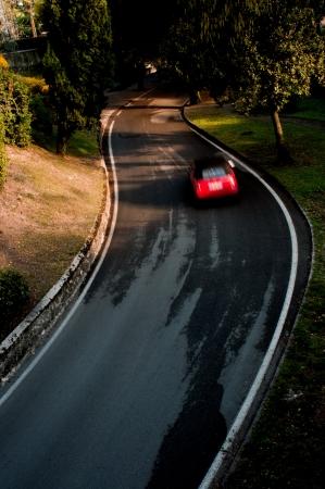 cornering: Red car cornering in a hill road