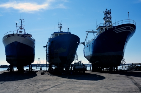 shipbuilder: three fishing boats under repair in a shipyard