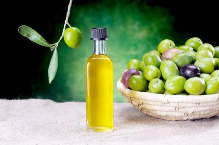 small bottle of olive oil with olives, traditional setting of still life