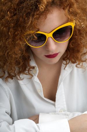naar beneden kijken: Roodharige meisje met een bril van ernstige blik naar beneden Stockfoto