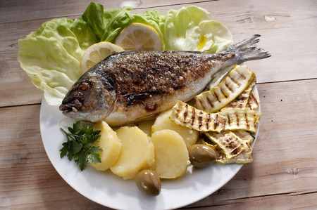 Delicious grilled fish bream, Mediterranean fish, with boiled potatoes and grilled zucchini photo