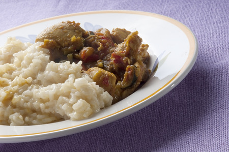Chicken curry with vegetables and rice plate on purple tablecloth photo