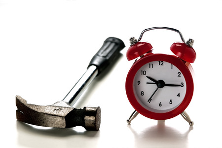 a clock and and a hammer, the concept of nuisance that causes the alarm clock in the morning
