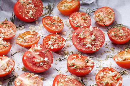 baking dish of tomatoes seasoned with garlic spices and sugar for the preparation of confit tomatoes Banque d'images