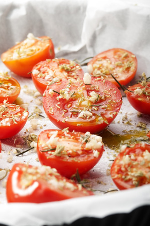 seasoned: baking dish of tomatoes seasoned with garlic spices and sugar for the preparation of confit tomatoes Stock Photo