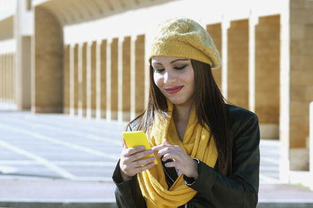 young  brunette: beautiful brunette girl looks at his phone to write a text message. modern urban setting Stock Photo