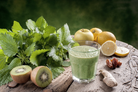 juice fresh vegetables: shake nettles with kiwi apples and ginger detox drink for a vegetarian diet Stock Photo