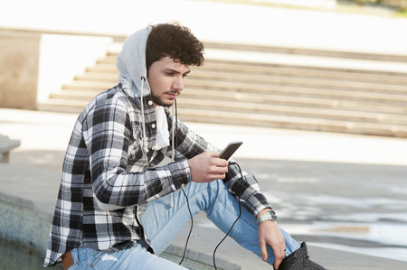 young stylish bearded man in Hoodie checkered shirt listening music in the city photo