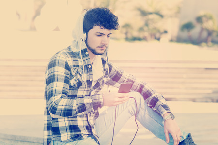 listening device: young stylish bearded man in Hoodie checkered shirt listening music in the city style