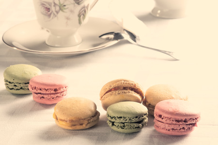 tea and biscuits: traditional french colorful macarons on a table for breakfast with filter in instagram tone