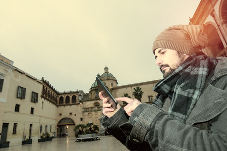 Young Man reading a tablet in a European square with a church on the background
