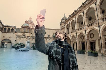 Jeune homme de prendre Selfie dans un carré européenne avec une église sur le fond