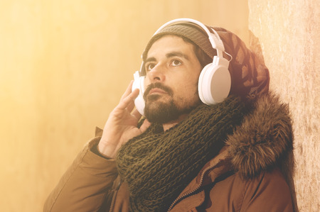 american downloads: a young man listens to music in an urban image of modern life warm tones style toned