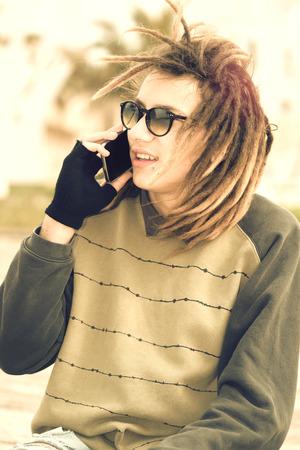 reggae: portrait de jeune homme en plein air avec des cheveux rasta souriant avec t�l�phone intelligent dans un concept de style de vie avec un filtre chaud appliqu�