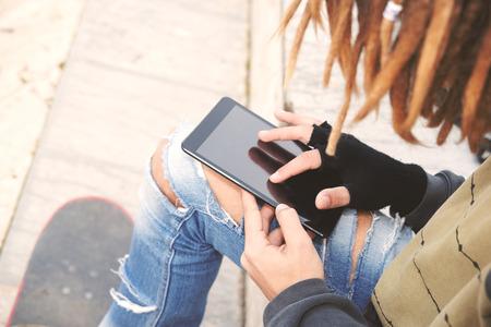 reggae: Image recadr�e homme pigiste avec des dreadlocks assis avec le message de frappe de tablette num�rique mise au point s�lective filtre chaude appliqu�e