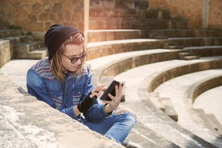 rasta hat: freelancer guy with dreadlocks sitting on staircase with digital tablet typing message warm filter applied