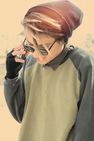 reggae: jeune homme en plein air avec des cheveux rasta avec t�l�phone intelligent dans un concept de style de vie avec un filtre chaud appliqu� s�lective focus sur les verres