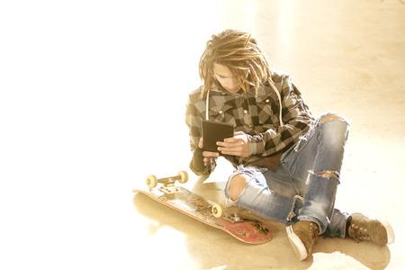 reggae: dreadlocks freelance gars assis avec le typage de tablette num�rique filtre de message chaude appliqu�e Banque d'images