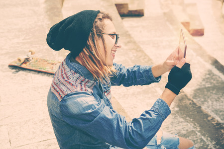 rasta hat: handsome guy with dreadlocks sitting on staircase taking selfie with tablet warm filter applied