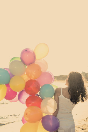 Happy woman having fun on the beach with multi colored balloons photo