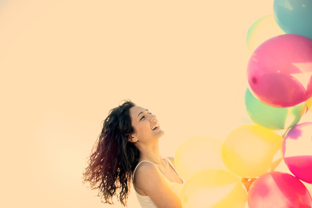 freedom woman: Happy woman having fun on the beach with multi colored balloons