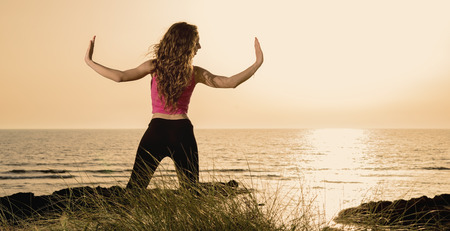 a young woman on the beach doing stretching warm filter applied photo