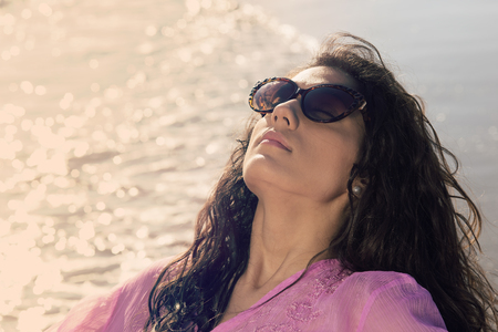 Mediterranean young girl with sunglasses on the beach warm filter