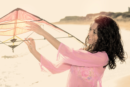 Mediterranean beautiful girl running on the beach with kite warm filter