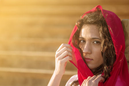 Mediterranean young girl with intense eyes with a red scarf