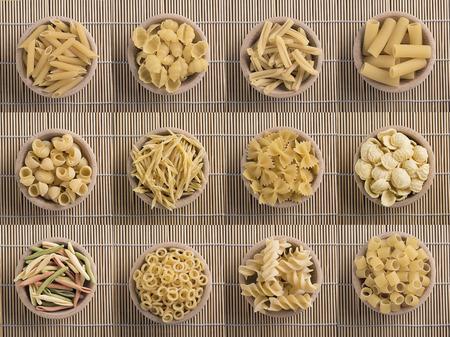 pastas: típicos de diversos tipos plato italiano de pasta cruda en un recipiente de madera