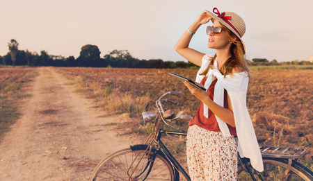 young woman with bike in  countryside working on tablet