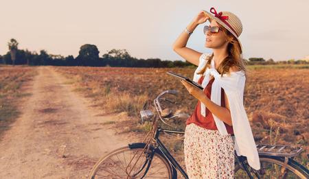 Mujer joven con la bici en campo trabaja en la tablilla Foto de archivo - 46724375