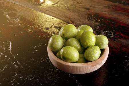 olive green: green olives on an wooden table after harvest