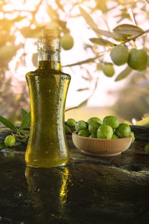 aceite de oliva: una botella de aceite de oliva extra virgen de oliva con árboles en el fondo Foto de archivo