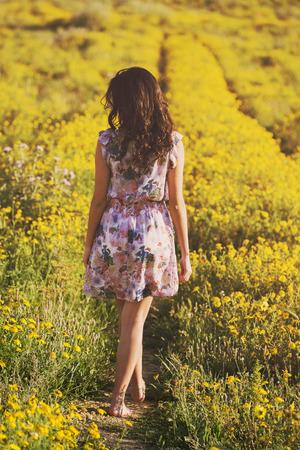 Vrij jonge vrouw op een madeliefjegebied bij zonsondergang. weglopen