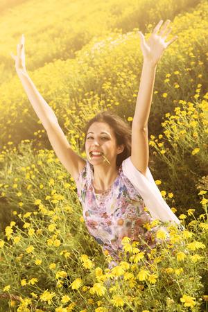 glücklich exultant und Freude Mädchen in einem Blumenfeld Standard-Bild