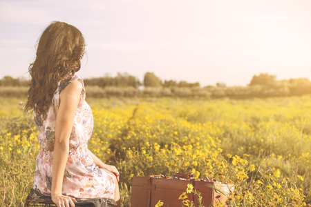 far away look: woman sitting in a field looking at the horizon Stock Photo