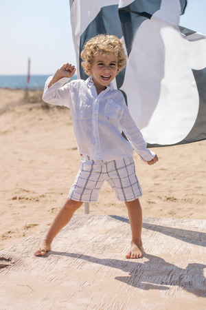 kidding: small child kidding standing on a beach in a sunny day Stock Photo