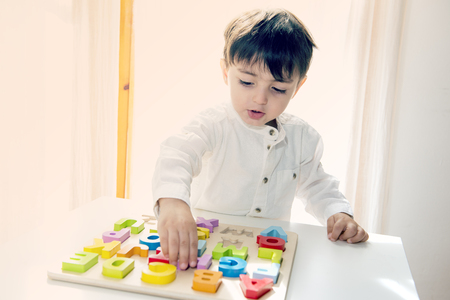 Child plays with wooden letters preschool game to develop intelligence