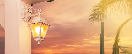 lintel: Lantern lit at sunset in a sky full of clouds Stock Photo