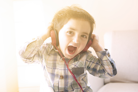 funny child listens to music with headphones in home-like atmosphere