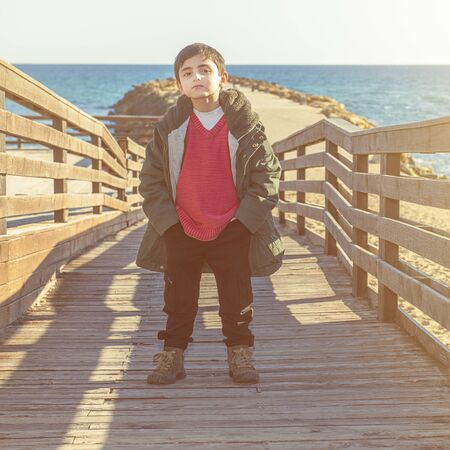 young boy with coat by the sea in an autumnal atmosphere Banque d'images