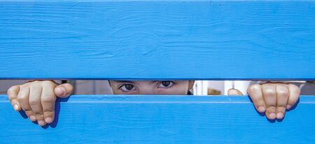 look of a child between the blue wooden planks Banque d'images