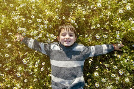 child smiling happy among the daisies in springtime day