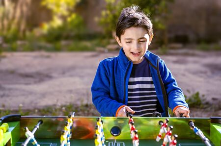 Happy child plays table soccer in a garden