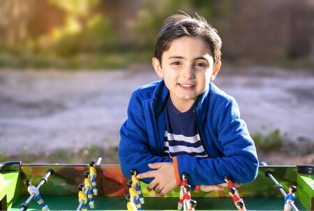 child plays table soccer in outdoor setting
