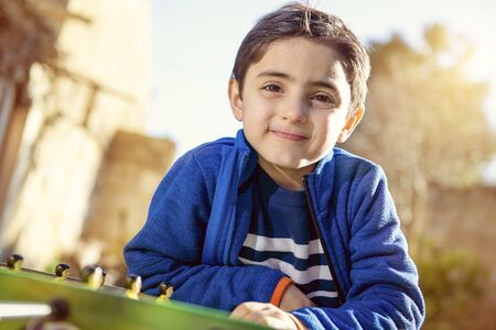 Child leaning against a soccer table smiling in outdoor setting Banque d'images