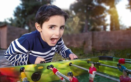 Child exults playing table soccer in a garden after scoring