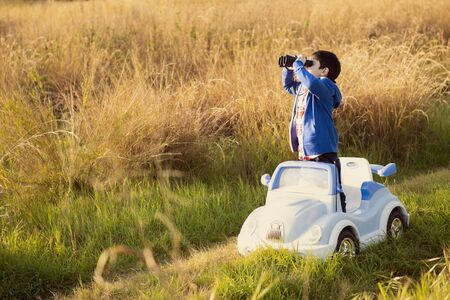 child in the countryside explores the world with his toy car. concept of freedom and discovery